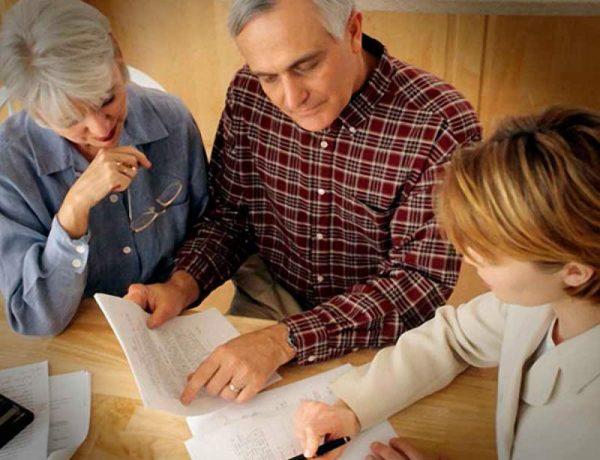 Пожилые мужчина и женщина оформляют документ