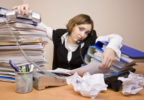 Девушка с кучей бумаг на столе