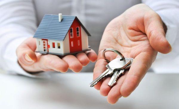 На руках человека модель дома и ключи