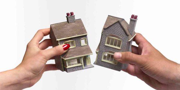 Руки мужчины и женщины, разделяющие макет дома на две части