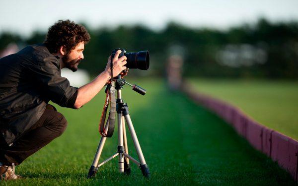 Фотограф и фотокамера на штативе