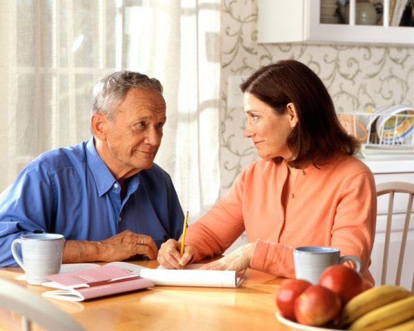 Пожилой мужчина и женщина оформляют документ