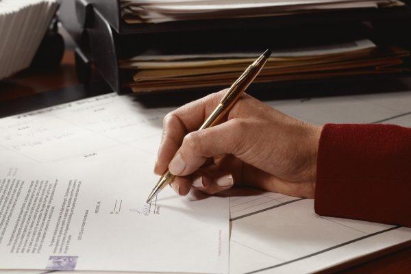 Рука, подписывающая документ