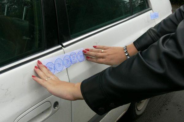 Судебный пристав опечатывает автомобиль