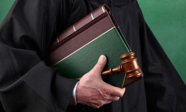 Судья в мантии, в руке которого книга и молоток