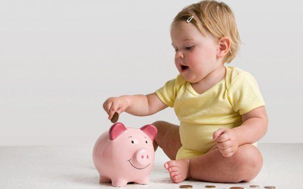 Ребёнок кладёт монетку в копилку