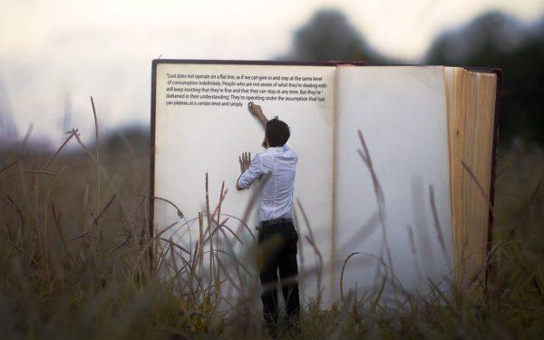Человек пишет в большой книге