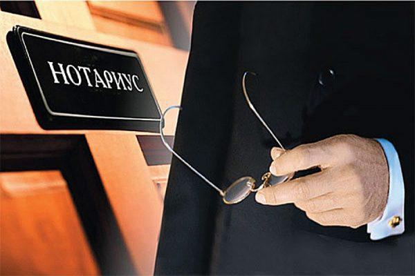 Человек с очками возле таблички «Нотариус»