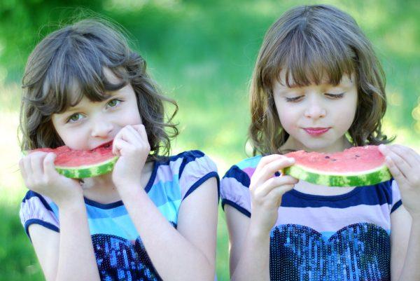 Девочки-близнецы едят арбуз