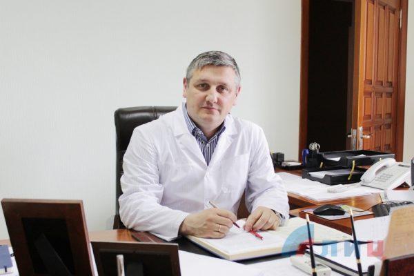 Мужчина в белом халате, сидящий за рабочим столом