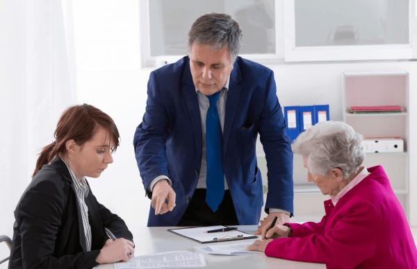 Мужчина и две женщины, одна из которых (пожилая) подписывает документ