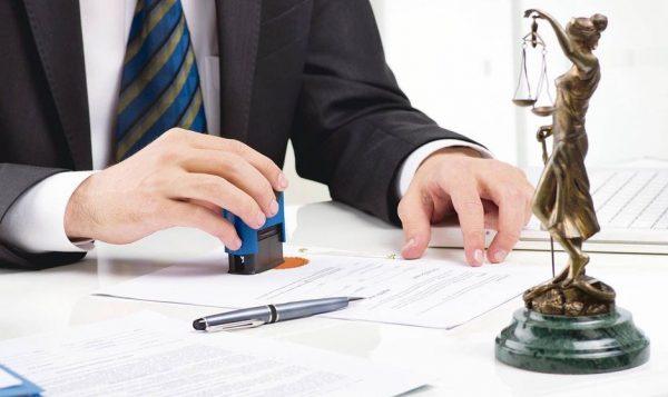 Мужчина ставит печать на нотариальном документе