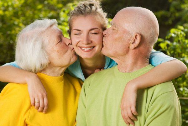 Пожилые люди целуют девушку в щёки