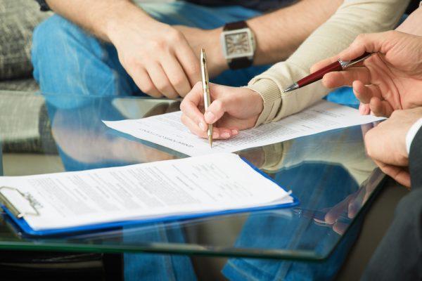 Женщина подписывает документы
