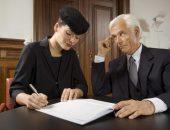 Женщина в траурной одежде подписывает документы