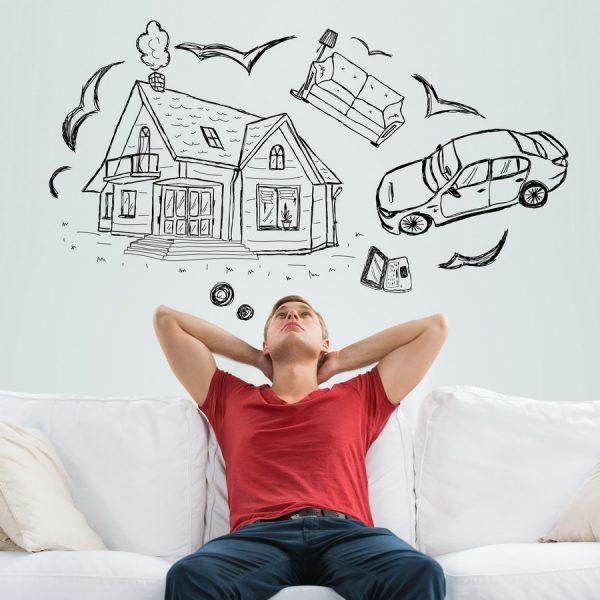Молодой парень сидит на диване, над его головой рисунки машины, домика и других объектов