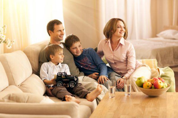 Мужчина, женщина и двое детей на диване смотрят куда-то в сторону