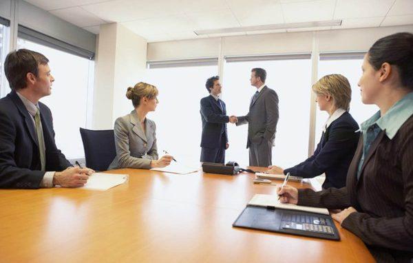 Сотрудники организации за столом переговоров на фоне мужчин, пожимающих друг другу руки
