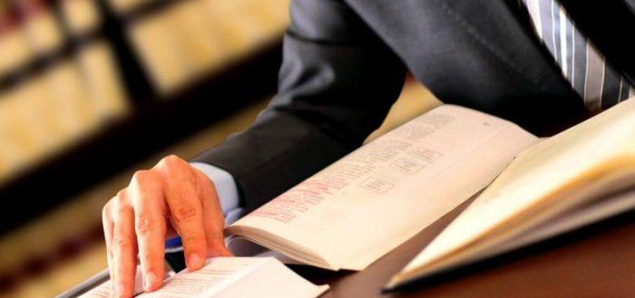 Справочники и документы на столе перед мужчиной