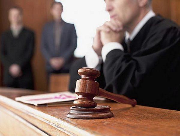 Судья сидит за столом, на переднем плане судейский молоток