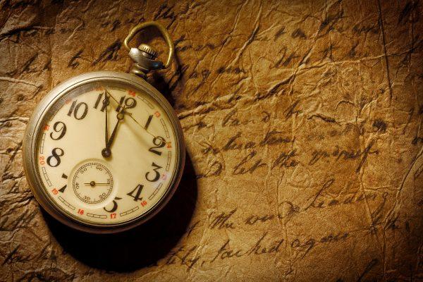 Часы на фоне исписанного листа