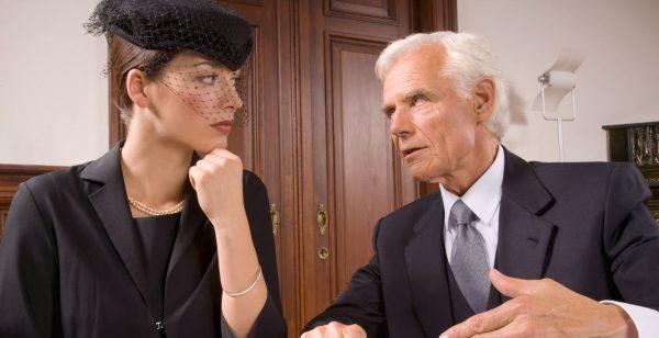 Женщина в траурном одеянии рядом с пожилым мужчиной