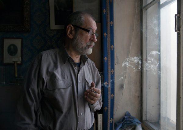 Пожилой мужчина курит