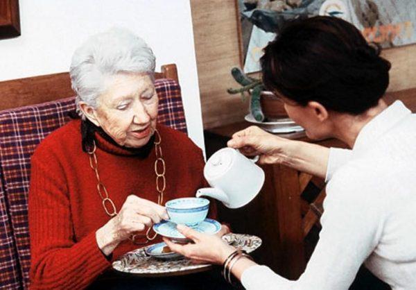 Пожилой женщине наливают чай