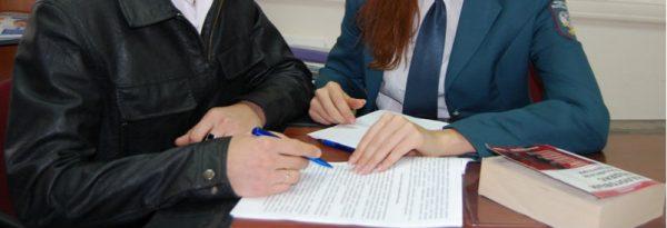 Человек подписывает документ в присутствии пристава