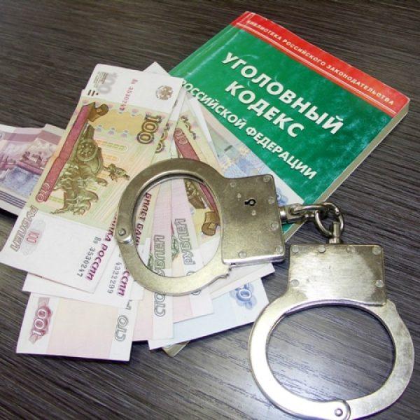 Денежные купюры, наручники и Уголовный кодекс на столе