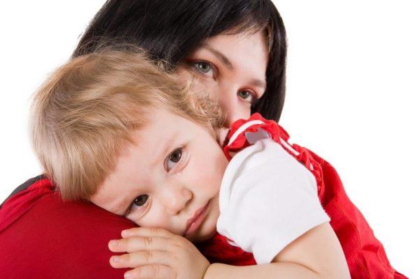 Грустный ребенок у мамы на руках