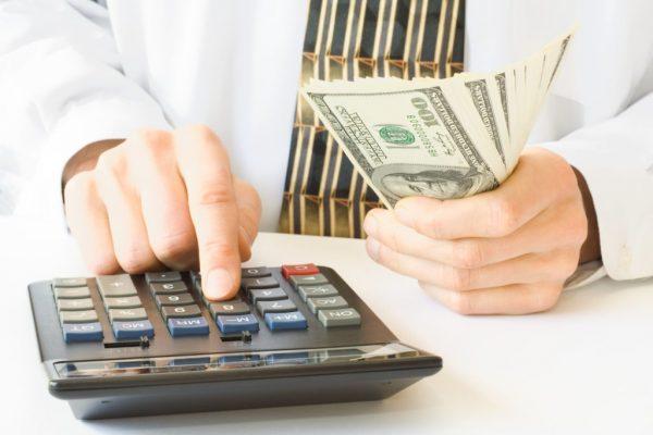 Мужчина с деньгами в руках считает на калькуляторе