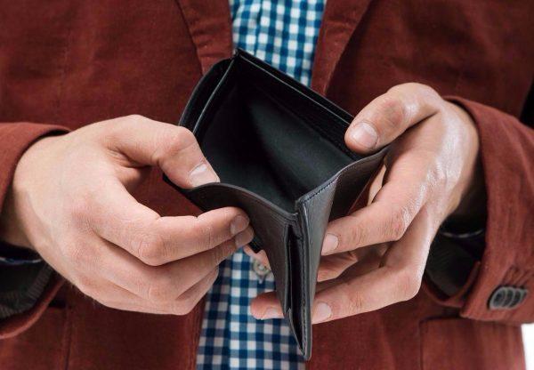 Мужчина раскрывает пустой кошелёк