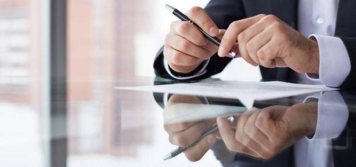 Мужчина за столом с листком и ручкой