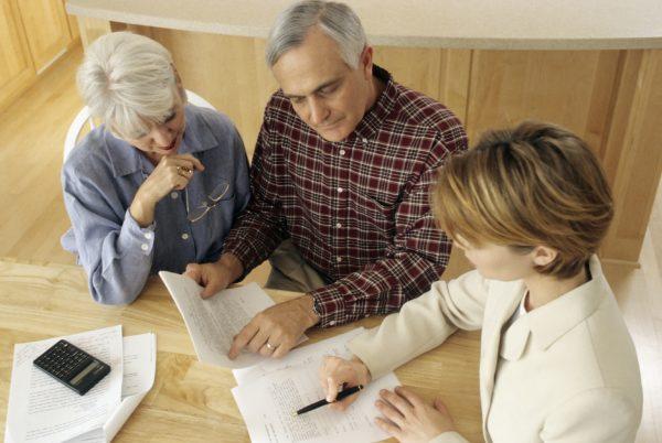 Пожилая пара заполняет документ