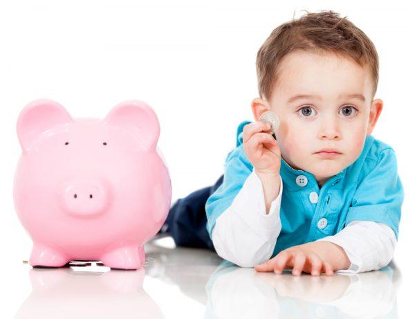 Грустный ребенок с монетой и копилкой