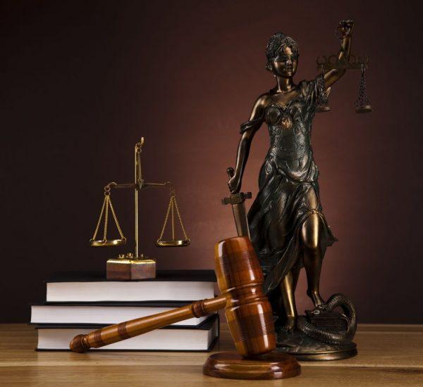 На столе находится молоток судьи, весы, правовая литература и Фемида