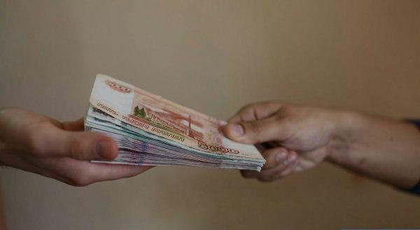 Рука одного человека кладёт деньги в руку другого человека