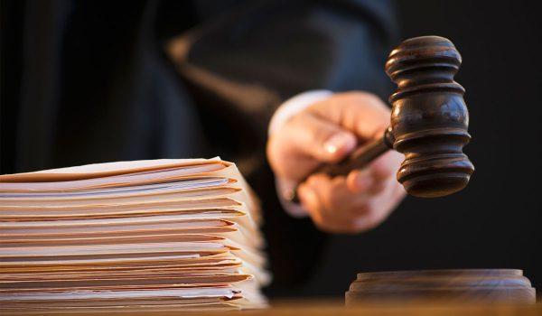 Судейский молоток в руке судьи и стопка бумаг