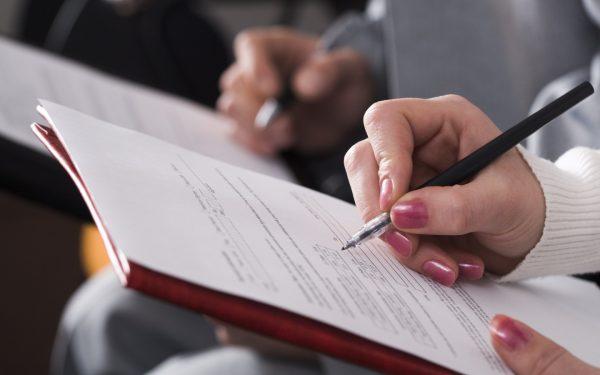 Руки женщины, заполняющей документ