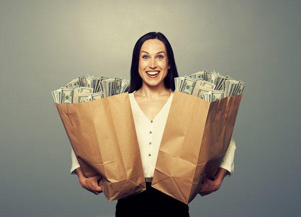 Женщина держит в руках два пакета денег