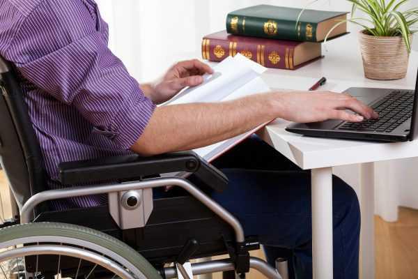 Мужчина на инвалидной коляске работает за компьютером