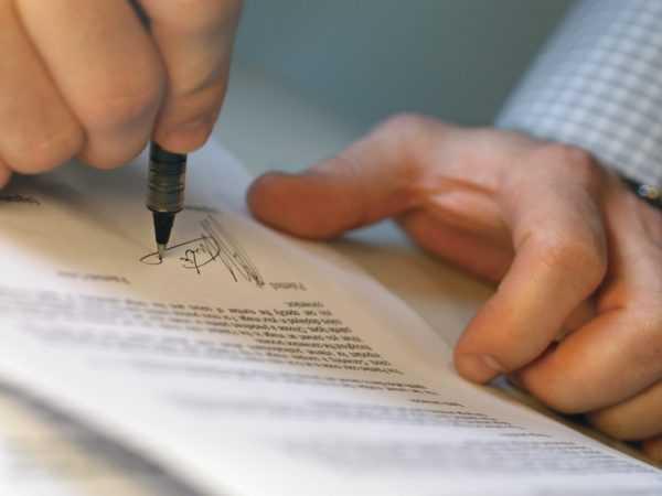 Мужчина ставить подпись на документе