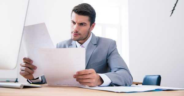 Мужчина за столом читает документы