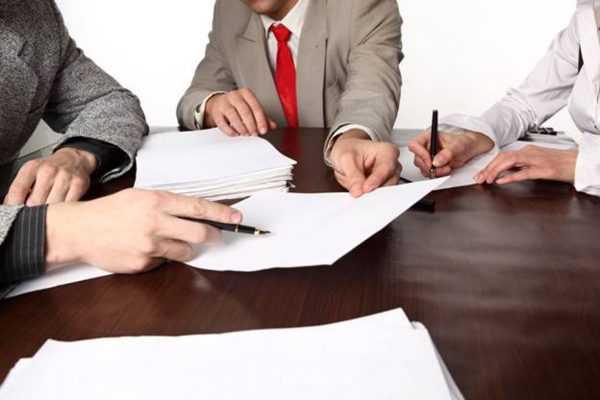 Люди с бумагами за столом