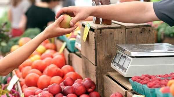 Продавец даёт яблоко покупателю