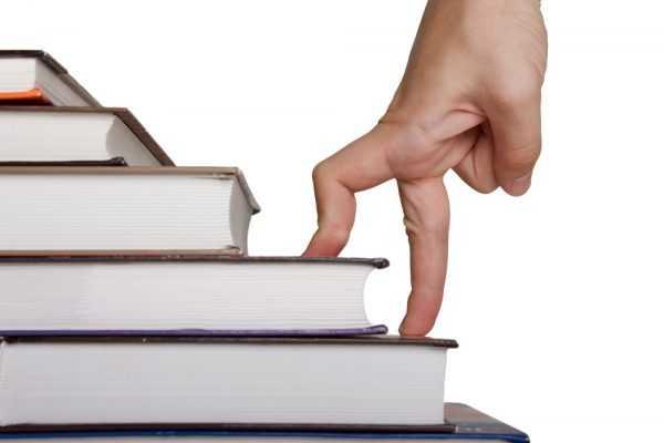 Пальцы изображают человека, который шагает по лестнице из книг