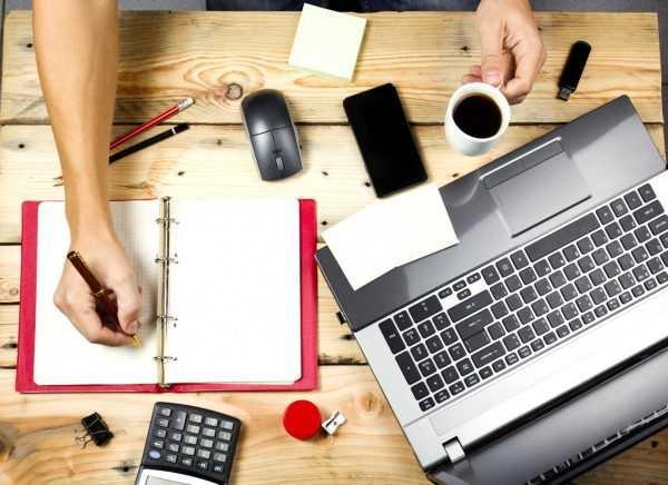 Человеческие руки и все символы делового человека: ноутбук, ежедневник, калькулятор и телефон