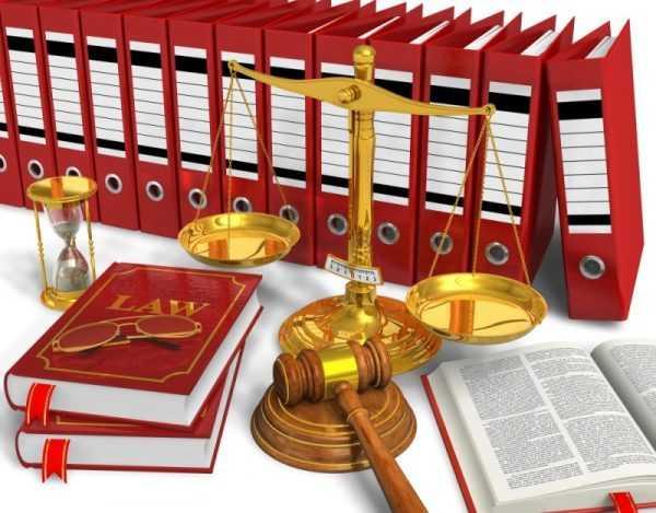 Судебная атрибутика на фоне стоящих папок