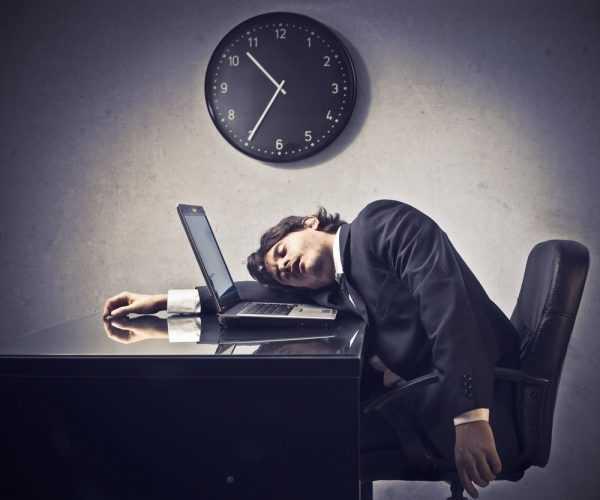 Мужчина в костюме спит, положив голову на рабочий стол